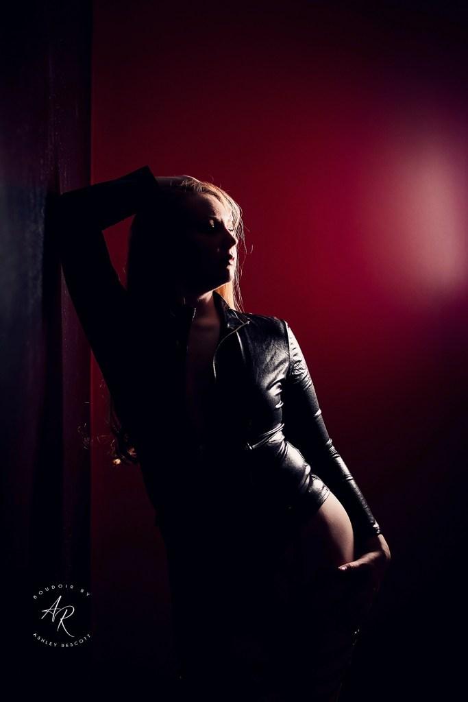 backlit image of boudoir model leaning against wall