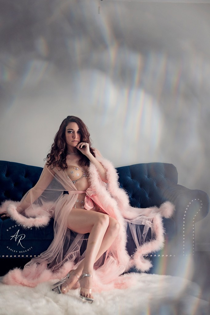 Boudoir portrait of woman in pink robe on blue couch utilizing in camera effects