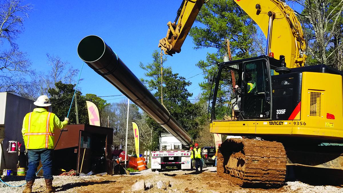 Web slings lifting sewage replacement pipe