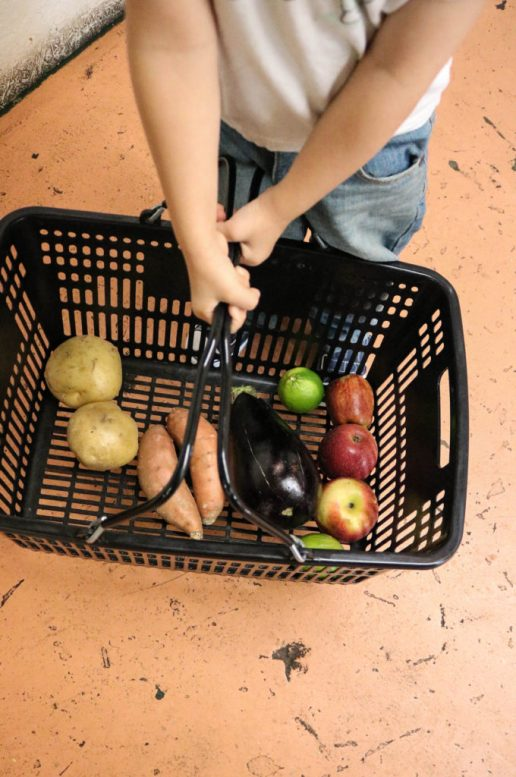 Basket of fruit and vegetables with children at farmers market