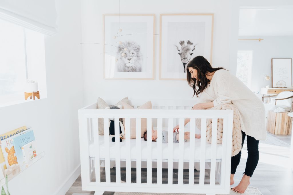 Baby Boy Nursery ideas featured by top Los Angeles life and style blogger, Ashley Hodges: mom looking at her baby led in his white crib, animal prints above the crib