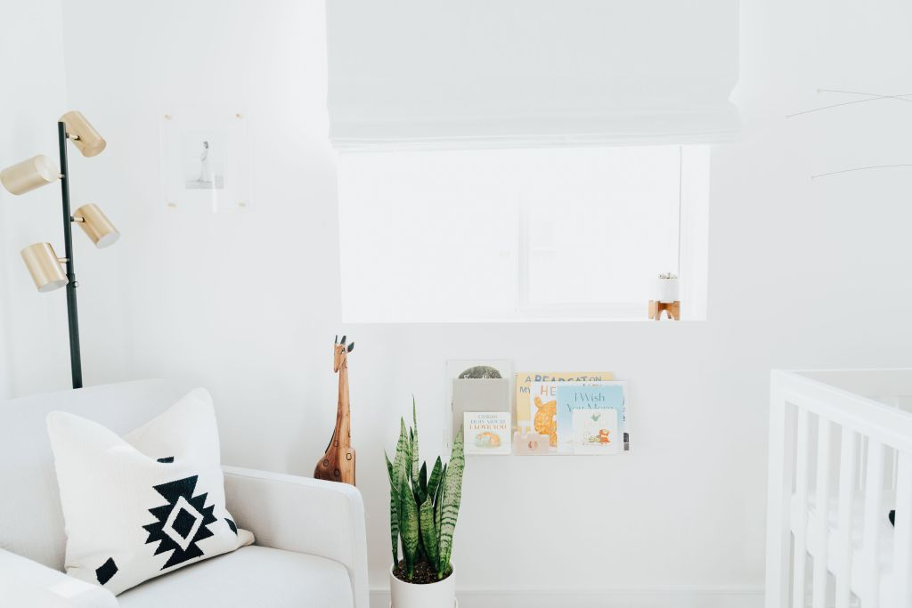 Baby Boy Nursery ideas featured by top Los Angeles life and style blogger, Ashley Hodges: white armchair, black and white cushion, giraffe tall figurine, plant, baby books, white blinds