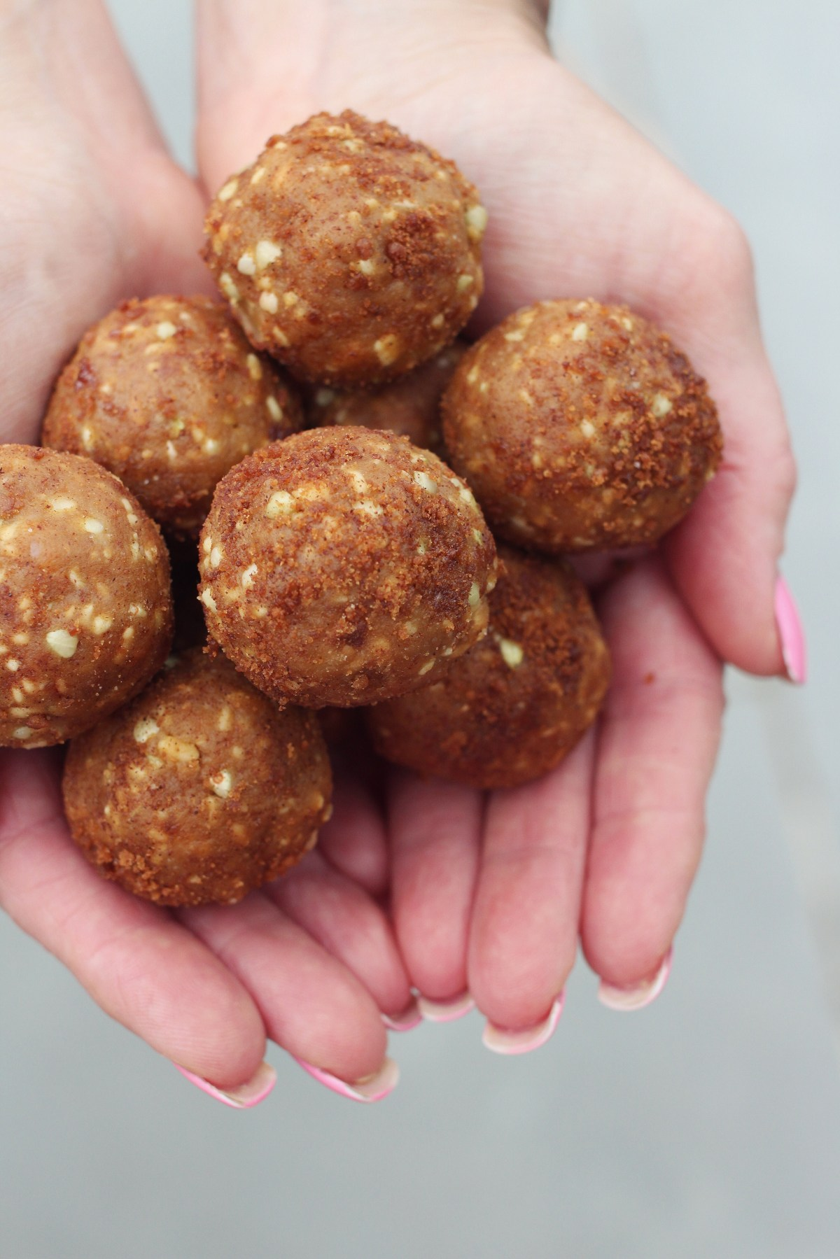 close-up overhead photo of peanut butter cookie dough balls being held in two hands together