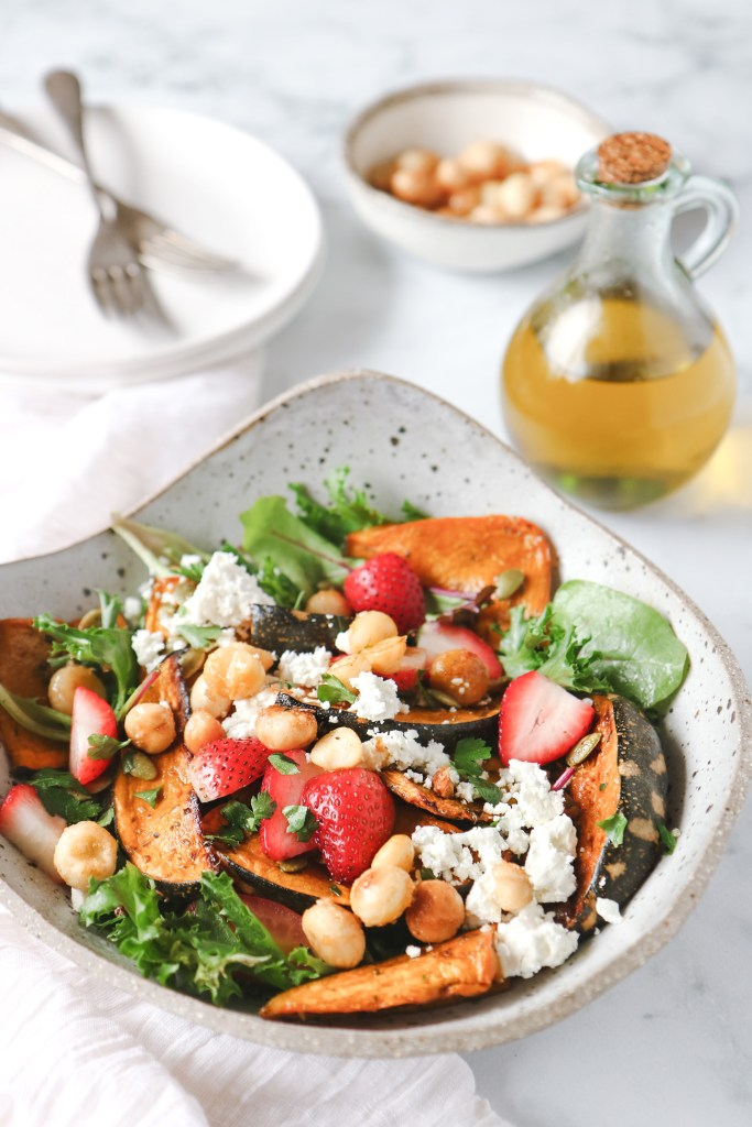 Bowl of maple roasted pumpkin and macadamia salad with strawberries, ggreens and herbs on a a marble table with olive oil and serving plates in the background.