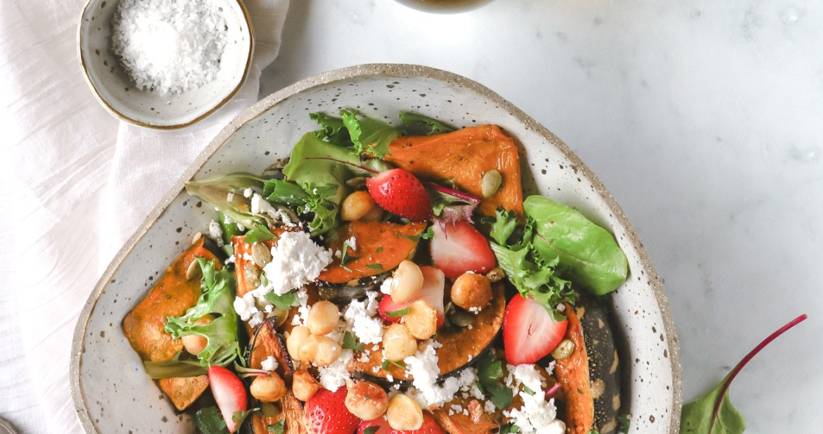 Overhead shot of maple roasted pumpkin, macadamia and strawberry salad on a marble table with side servings of sea salt flakes, extra macadamias and olive oil
