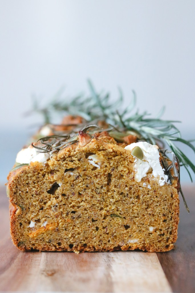 Font-on photo of pumpkin, feta and chive loaf sitting on a wooden board with fresh rosemary on top