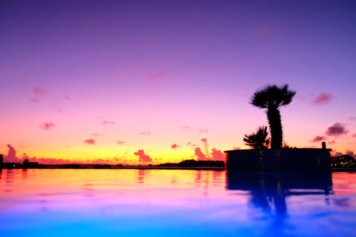 newstead resort in bermuda picture of the sunset over the infinity pool and ocean. Palm trees and pool