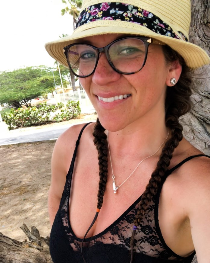 smiling girl in Aruba after scuba diving she has braided hair and is wearing a black one piece swimsuit and hat