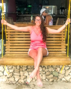 smiling girl on a swing in aruba after scuba diving she has beach wavy hair and is wearing a pink shir and white shorts from Express