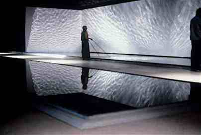 """Elizabeth Ogilvie. """"The Liquid Room"""", Water, roofing materials, timber, paint, aluminium, floods, video projection, fans, pumps, benches, 72 m x 13 m, Forth Ports Warehouse, Kirkcaldy Dock, Fife, 2001"""