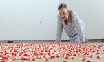 """""""Searle contemplates the red and white capsules that rain, one every three seconds, from the ceiling. Photograph: Christian Sinibaldi for the Guardian"""""""