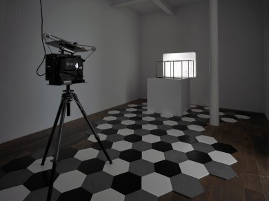 Untitled (Dihedra), 2010-12 16mm projection, steel cage, steel tiles, plinth, projector, looper, tripod. Dimensions vary