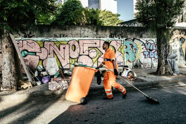 A street cleaner at work near homeless people in Lapa. Photograph: Nicoló Lanfranchi/The Guardian