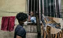 Wearing a facemask, Ricardo Fernandes, 30, takes parcels of necessities around the City of God favela Photograph: Nicoló Lanfranchi/The Guardian