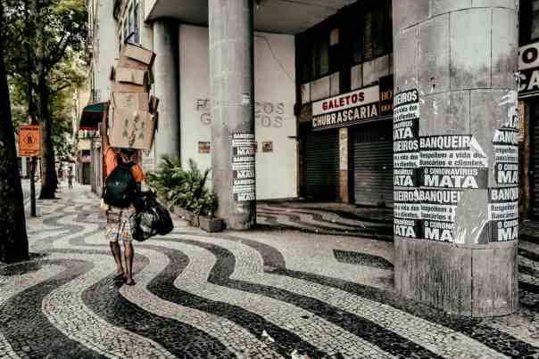 A man in Rio Centro walks next to a poster that says: 'Bankers, respect the lives of workers and customers, coronavirus kills.' Photograph: Nicoló Lanfranchi/The Guardian