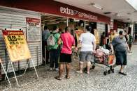 People wait to shop outside a supermarket in Lapa. Photograph: Nicoló Lanfranchi/The Guardian