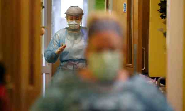 "Nurses wearing protective gear rush out of a care home's ""red zone"" for people sick with coronavirus. Photograph: Frank Augstein/AP"