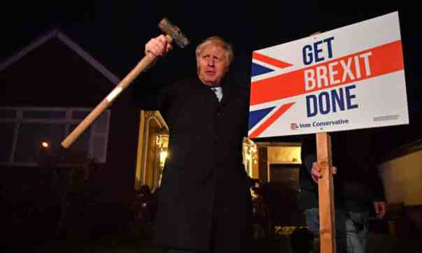 'Boris Johnson has pounded away at the domestic side of Brexit and distorted the shape of British politics.' Johnson poses with a sign in Benfleet, Essex, December 2019. Photograph: Ben Stansall/AFP/Getty Images