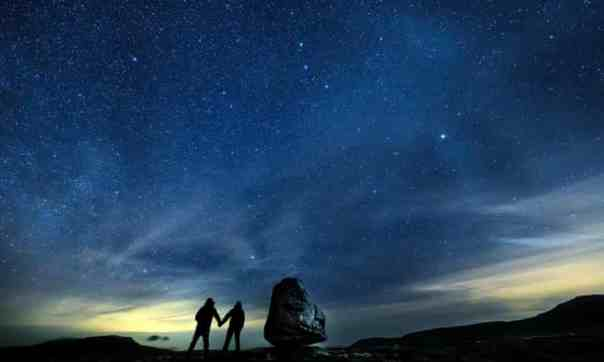 Walkers look up into the night sky above Twistleton Scar in the Yorkshire Dales national park - the largest dark sky reserve in the UK. Photograph: Danny Lawson/PA