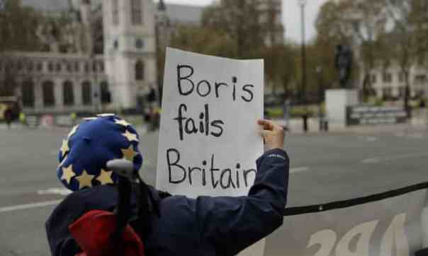 An anti-Brexit protester holds a placard after Boris Johnson drove past to attend prime minister's questions on Wednesday. Photograph: Matt Dunham/AP