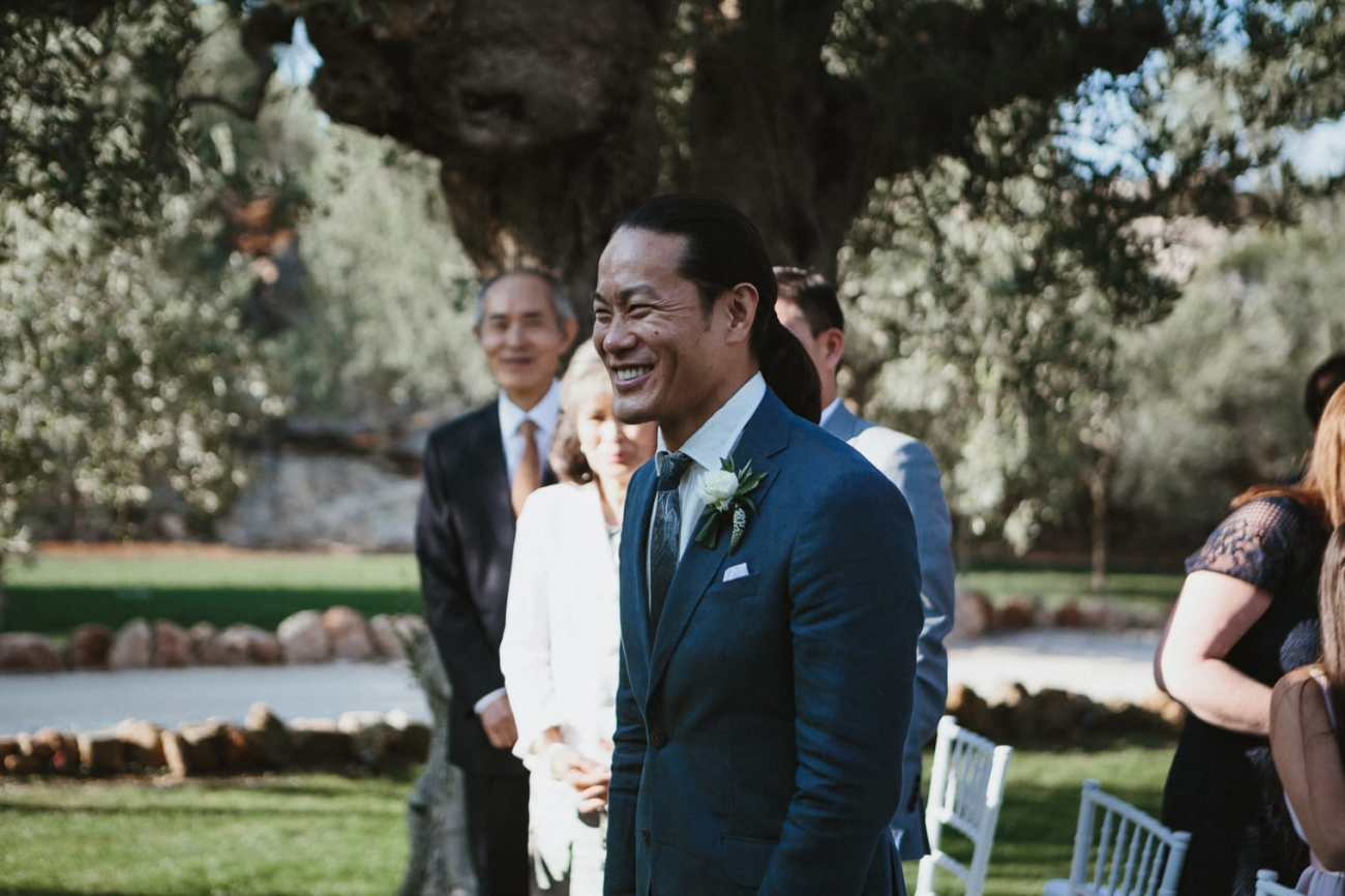 Groom looking happy as he waits for bride at the altar in Italy for their destination wedding