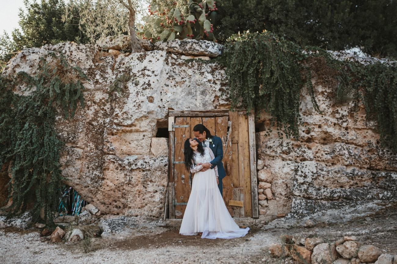 Bride and groom together under a cactus tree in Italian for their italy destination wedding