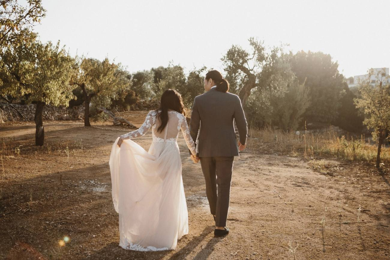 Puglia Wedding Photographer captures bride wearing Hermoine de paula gown in italy walking through an olive tree field