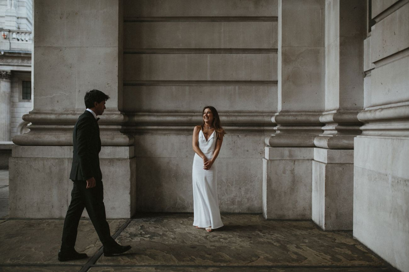 Bride smiling at groom walking towards her during wedding portraits in london