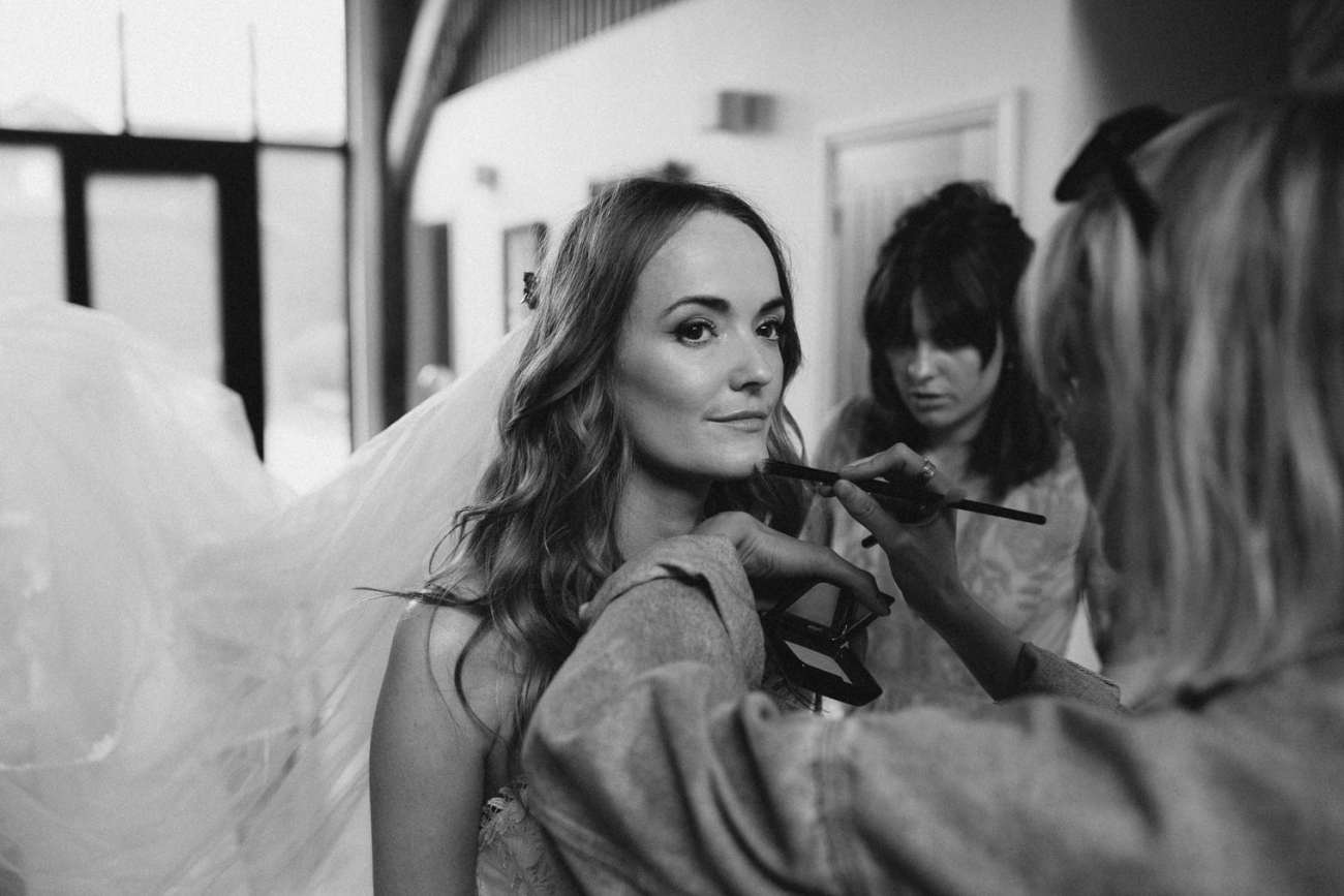 Bride getting last minute makeup touches before wedding