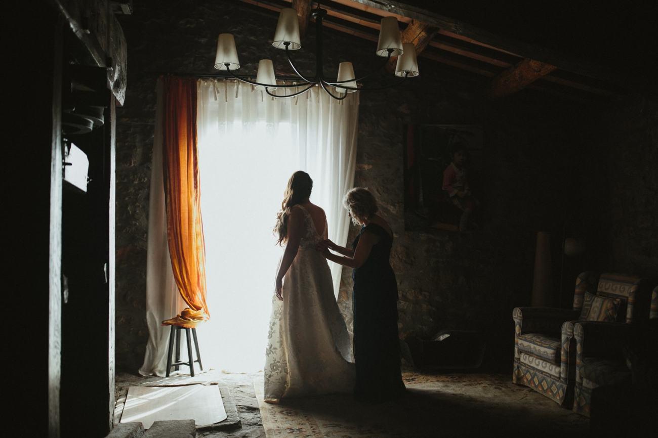 bride getting into Jenny Yoo gown before her wedding at la garriga de castelladral