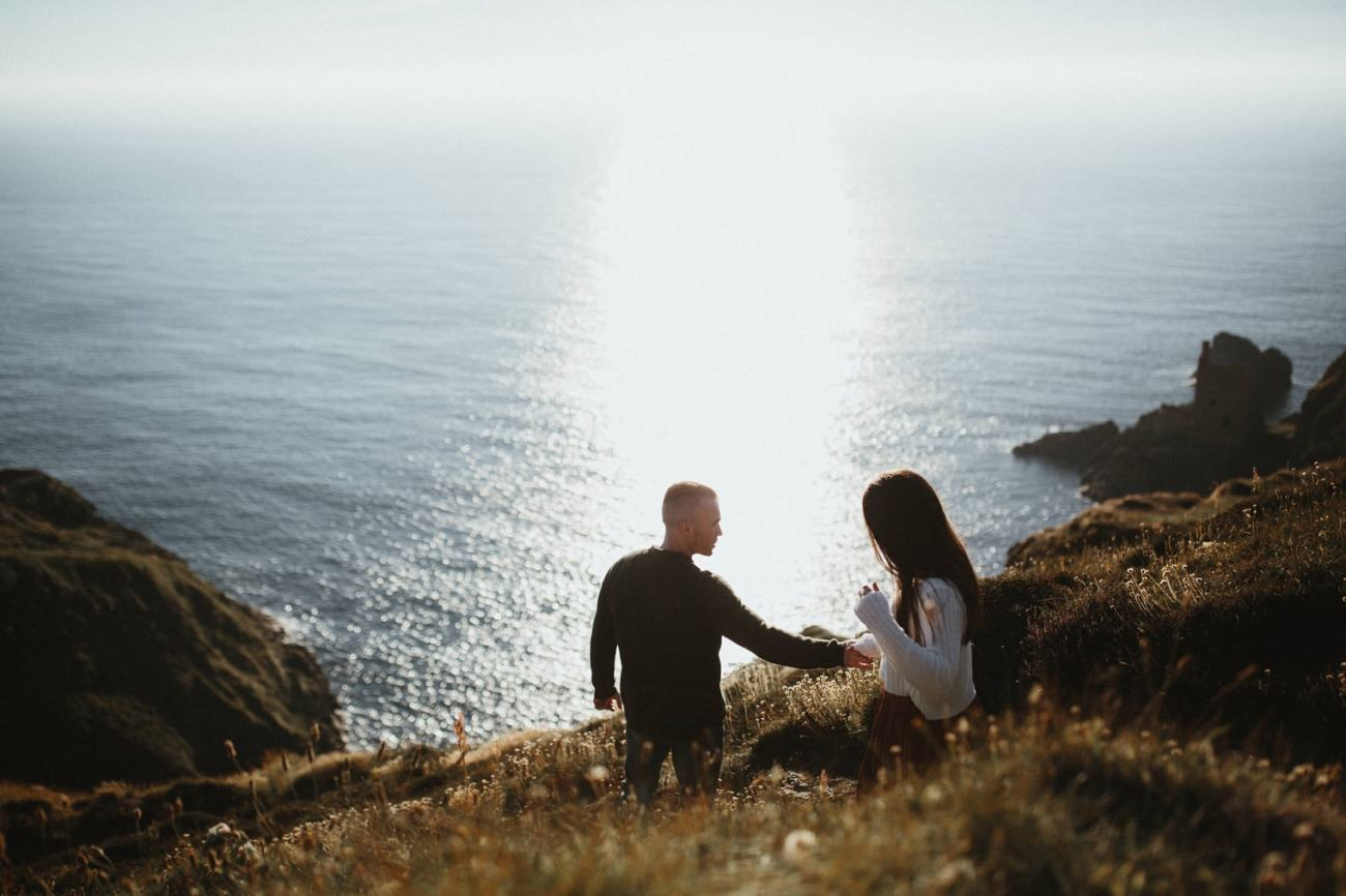 couple exploring cornish coastline during engagement shoot