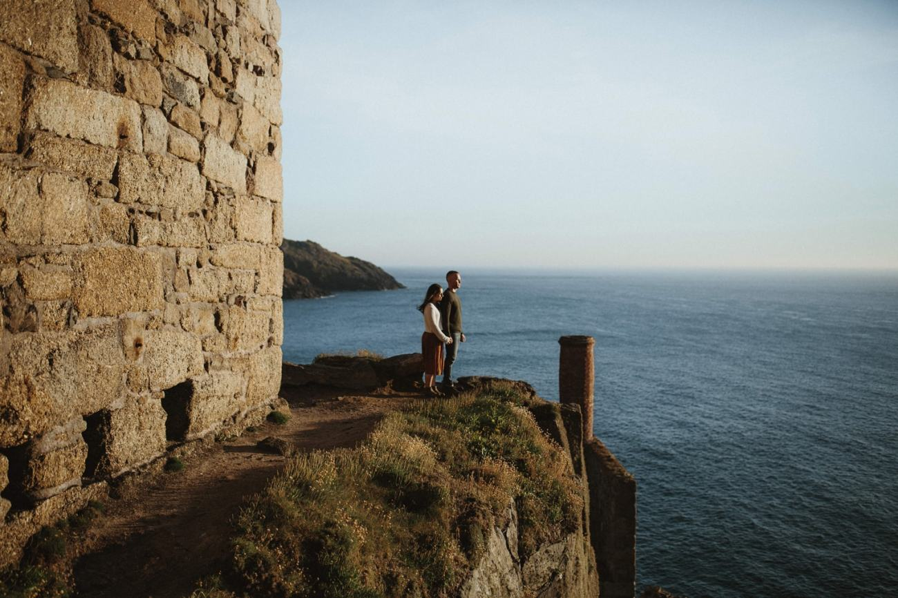 Couple standing together on a sea edge next to cornish tin mine