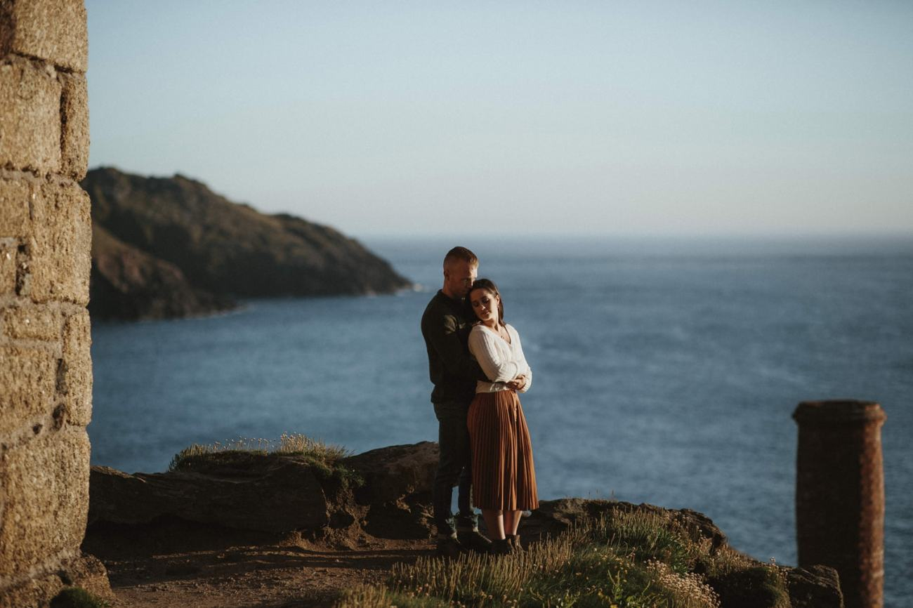 couple hugging each other on cornish coast during engagement shoot