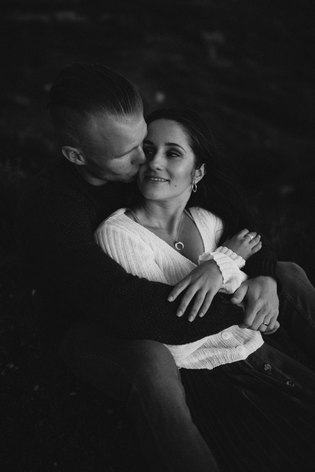 black and white image of couple cuddling during engagement session
