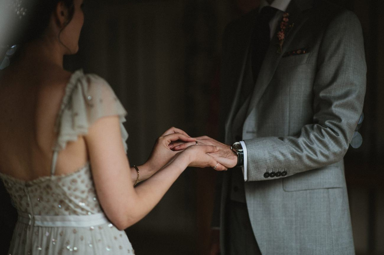 bride and groom exchanging vows during their english barn wedding