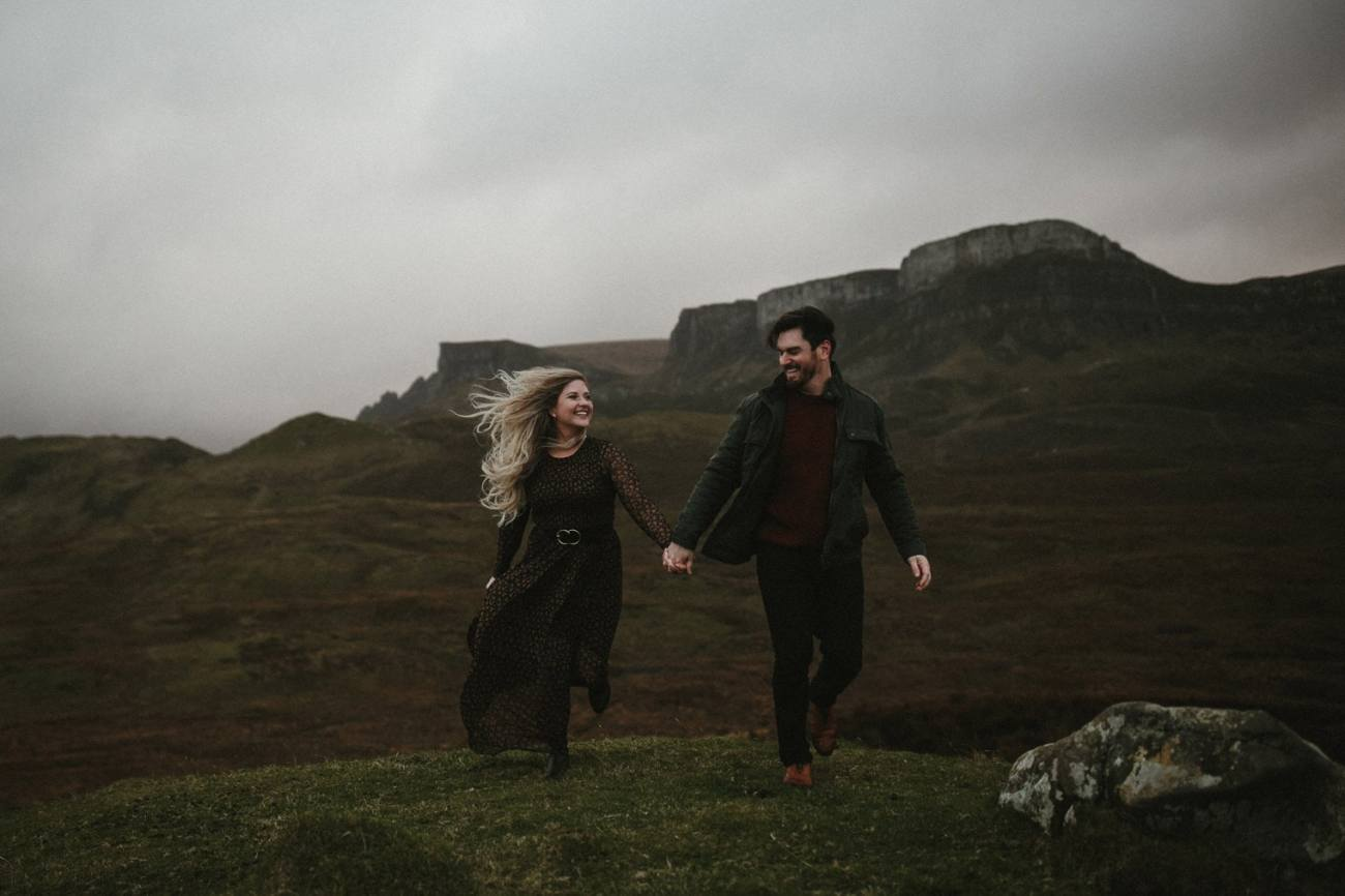 couple running in the mountains in Isle of Skye during their Isle of Skye Anniversary session