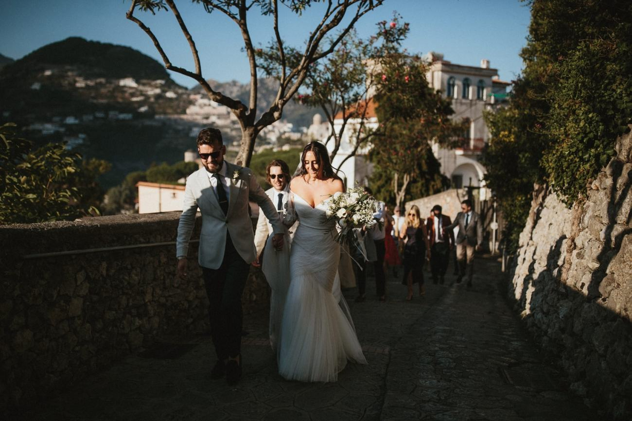 Bride and Groom and wedding guests walking to wedding reception in Ravello, Italy