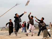 Children chase a kite as they play on the second day of Eid al-Adha in Kabul November 7, 2011. REUTERS/Umit Bektas (AFGHANISTAN - Tags: RELIGION SOCIETY TPX IMAGES OF THE DAY)