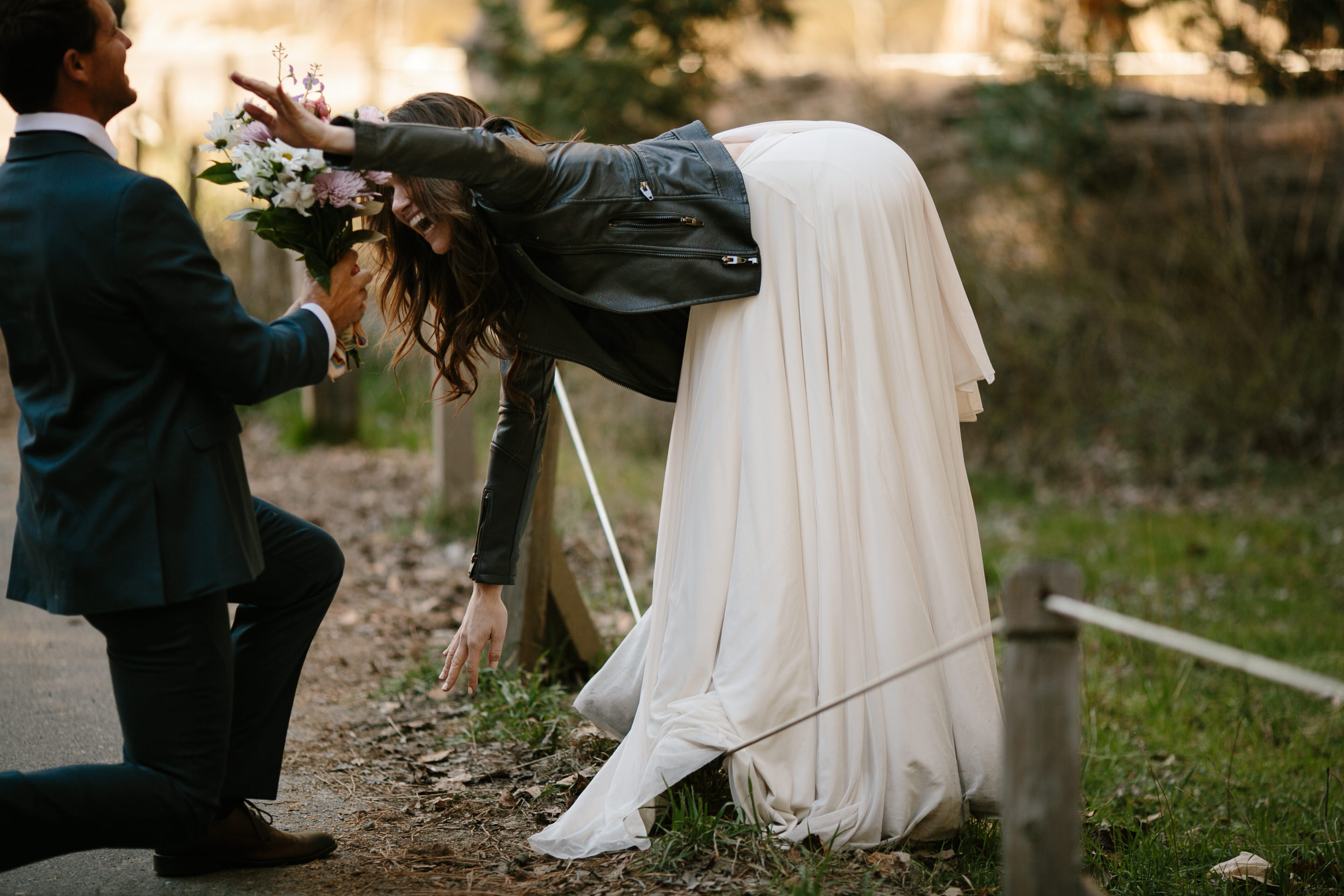 Flowers in hand, Ryan kneels before his bride while she slack lines in her wedding dress at Yosemite