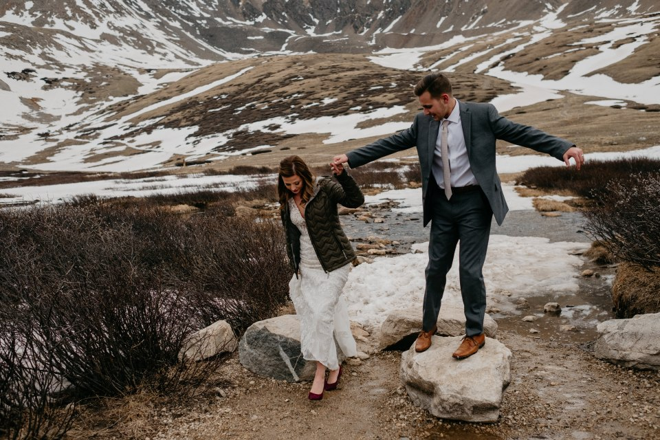 Blayke helps his new bride across the rocks at the trailhead during their Colorado elopement session.