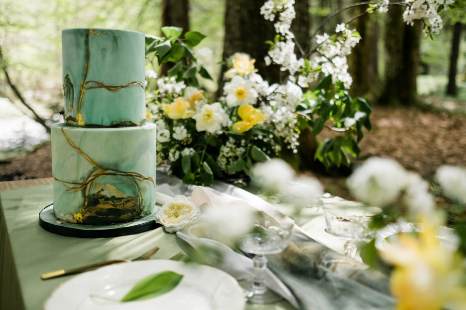 The greens and golds of this whimsical table setting pair perfectly in this woodland forest setting.