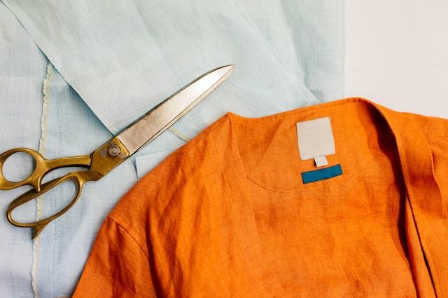 Orange shirt laying on cutting board with scissors