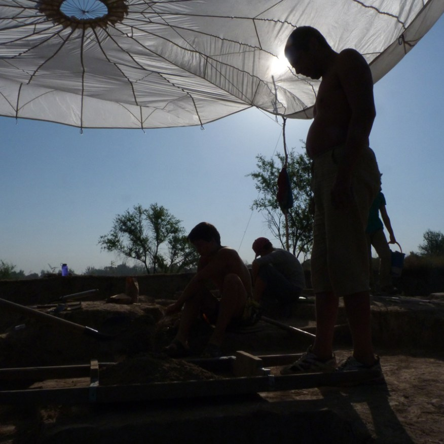 Three people in shadow under parachute tent, digging.