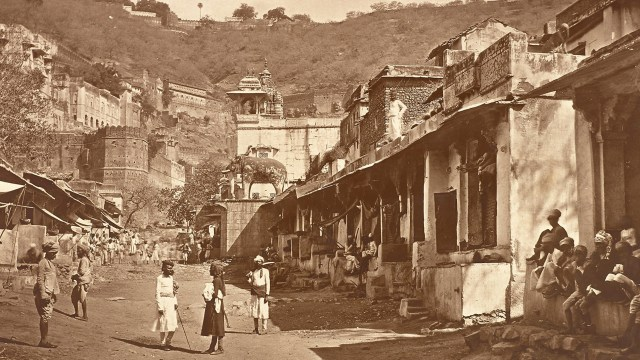 Sepia tone photo of a street Bhoondi with some figures along it, with mountains in the background.