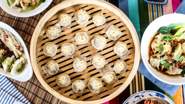 Bamboo steamer filled with steamed dumplings., surrounded by dishes of other variously shaped dumplings.