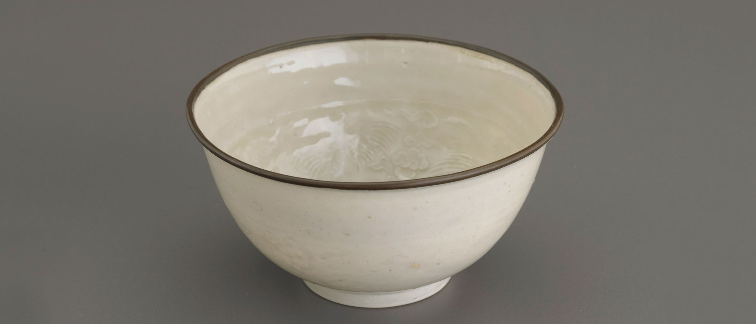 A white bowl with a molded brown decoration