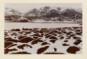 Snowy landscapes with dark rocks and mountains.