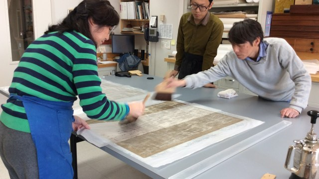 three conservators holding brushes and working on paper work