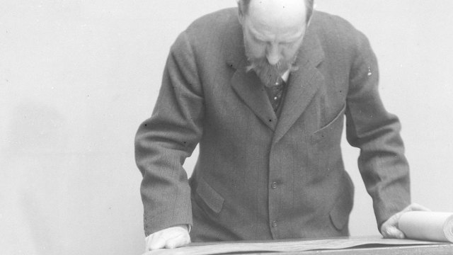 Archival image of Freer studying a scroll
