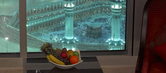 A bowl of fruit sits before a window looking down into a crowded square.